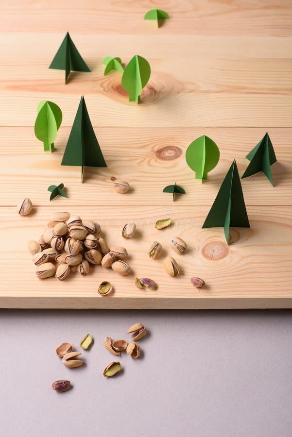 Pistaches sur la surface en bois, arbres verts de papier Concept naturel sain de nourriture images libres de droits