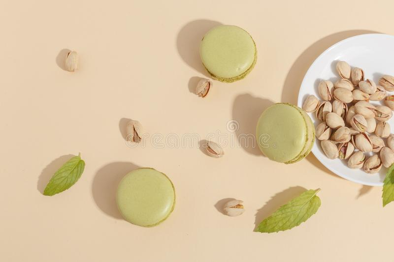 Pistachio cake makaroons and forex pistachios on a beige background. Top view. Tasty sweet dessert almond green cream food cookie delicious chamomile assorted royalty free stock image
