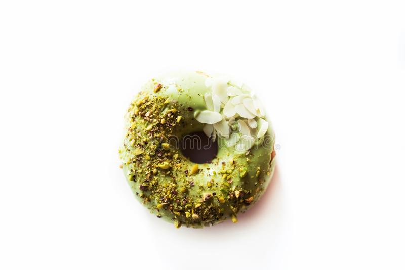 Pistachio donut on a white background. Pistachio donut with chopped pistachio and sliced almonds- on a white background royalty free stock photo