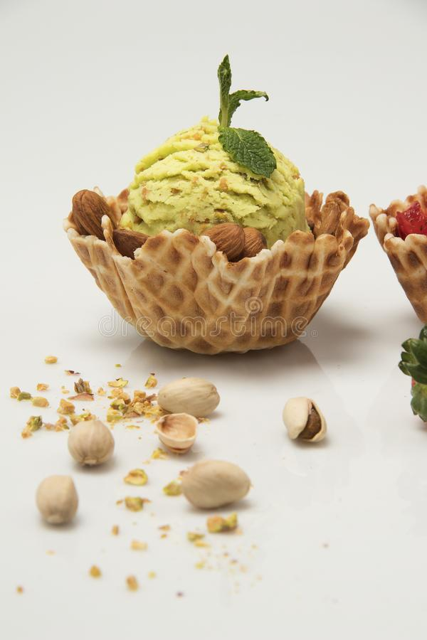 Pistachio ice cream in cookie cornet basket white background royalty free stock photography