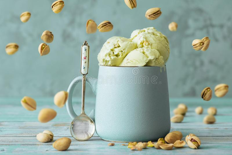 Pistachio ice cream in cup . Pistachio ice cream in cup on wooden table royalty free stock photos