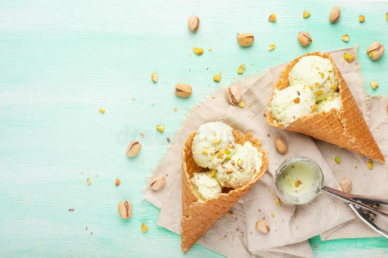 Pistachio ice cream with pistachio nuts and a spoon for ice cream on a light mint background. Top view, Flat lay. Summer mood.  royalty free stock photography