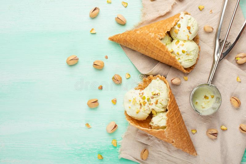 Pistachio ice cream with pistachio nuts and a spoon for ice cream on a light mint background. Top view, Flat lay. Summer mood.  stock image