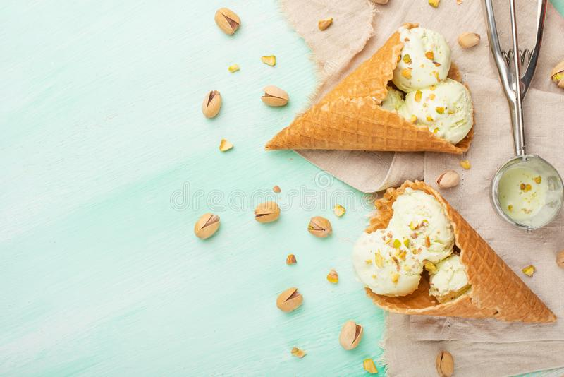 Pistachio ice cream with pistachio nuts and a spoon for ice cream on a light mint background. Top view, Flat lay. Summer mood.  royalty free stock photo