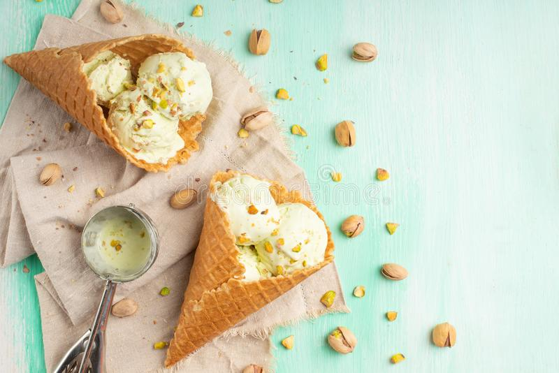 Pistachio ice cream with pistachio nuts and a spoon for ice cream on a light mint background. Top view, Flat lay. Summer mood.  stock photo