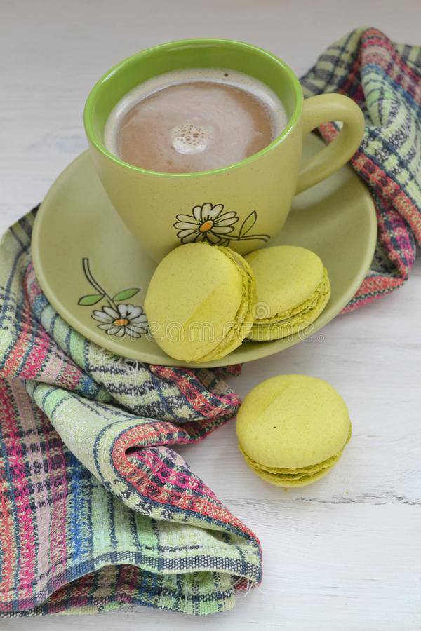 Pistachio macaron macaroon cookie dessert from France, vertical photo with coffee cup stock images