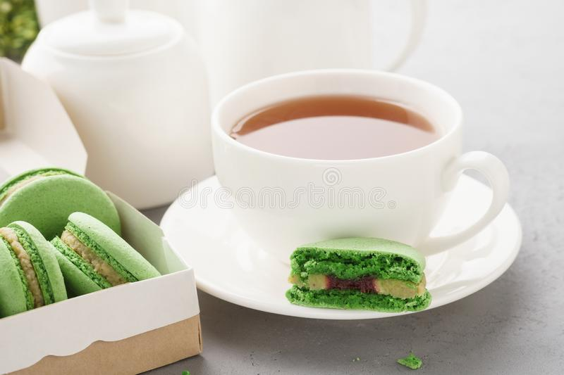 Pistachio macarons with berry filling and tea for dessert royalty free stock photography