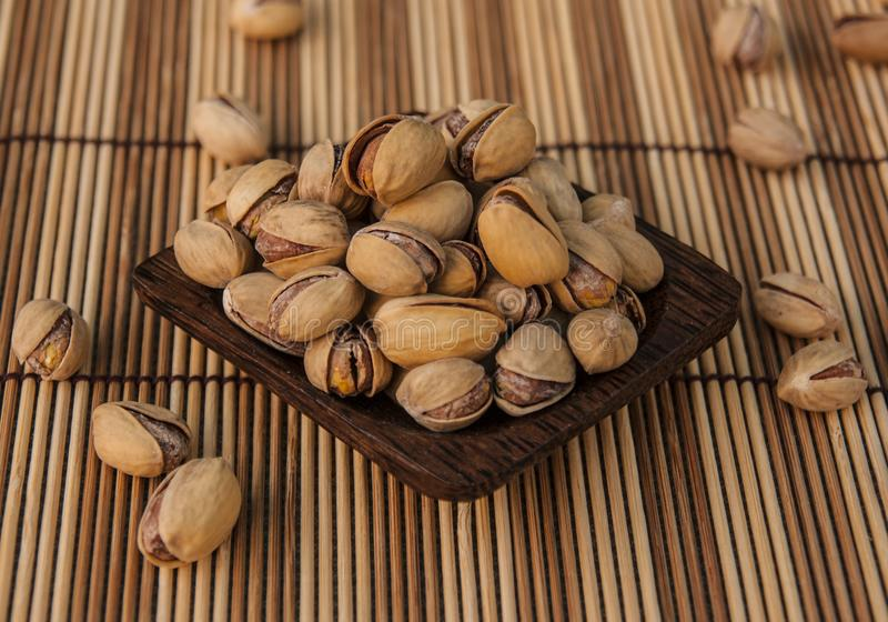 Pistachio nuts background. Pistachio nuts on wooden background royalty free stock photos