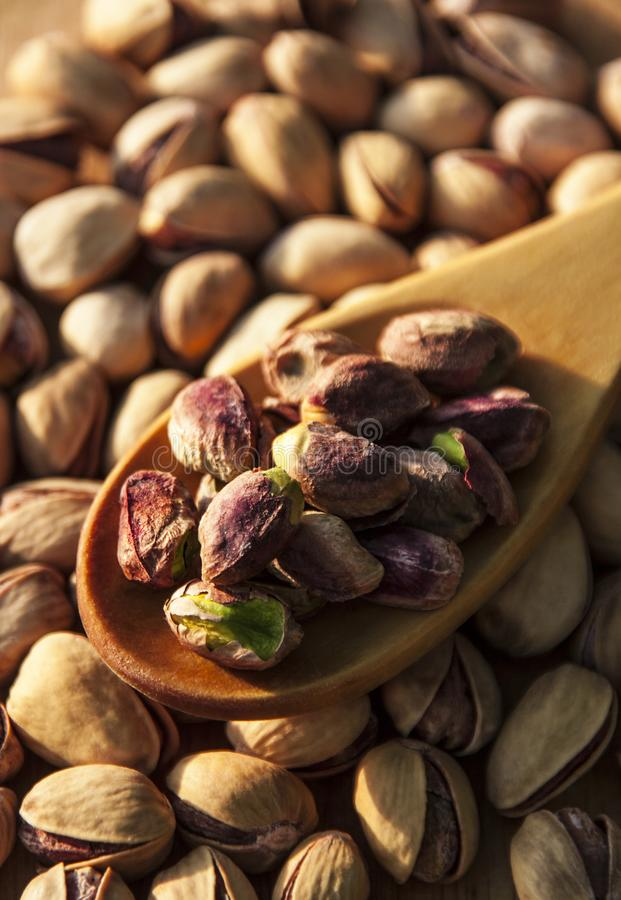 Pistachio nuts background. Pistachio nuts on wooden background stock photo