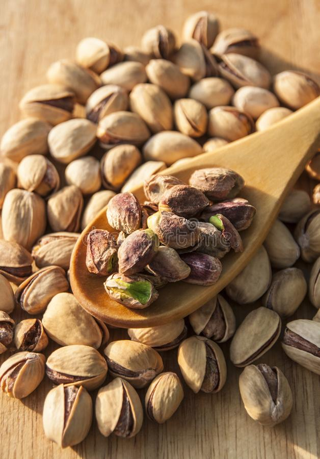 Pistachio nuts background. Pistachio nuts on wooden background royalty free stock images