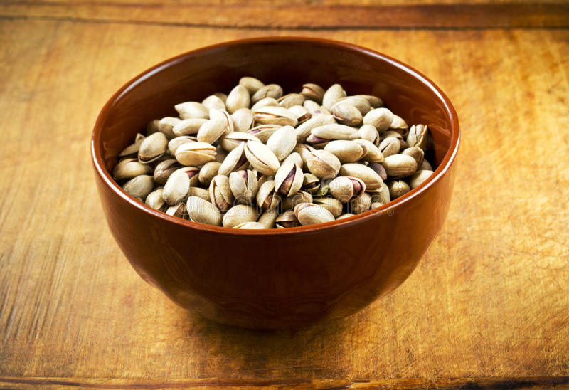 Pistachio nuts. In a bowl on wooden table, ready to eat royalty free stock photo