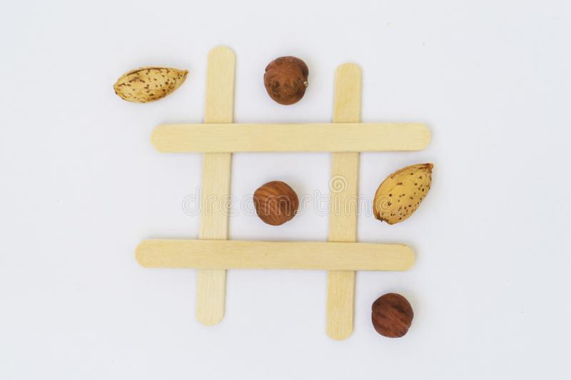 Pistachio nuts and dried fruits on the field for the game of tic-tac-toe on a white background royalty free stock image