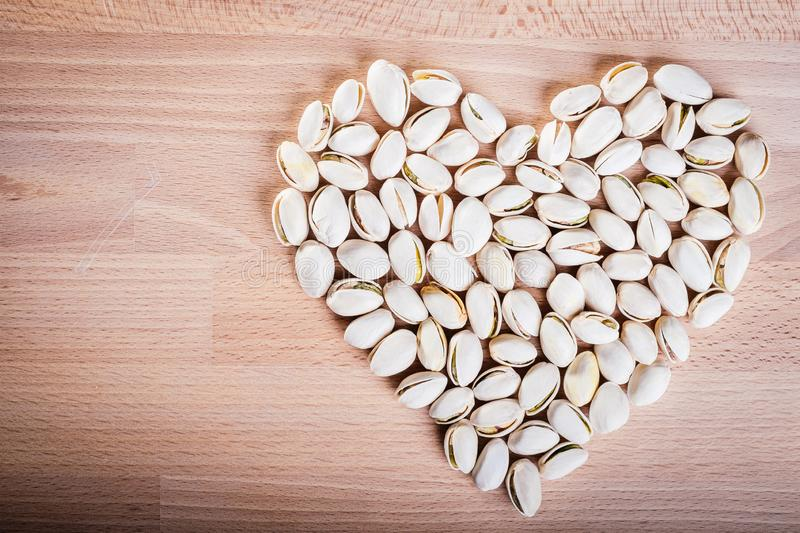 Pistachio nuts forming a heart-shape on wooden floor background stock photos