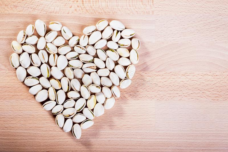 Pistachio nuts forming a heart-shape on wooden floor background royalty free stock photography