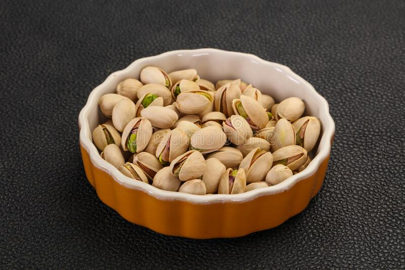 Pistachio nuts heap. In the bowl royalty free stock photography