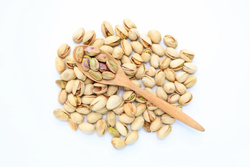 Pistachio nuts isolated on white background with wooden spoon. Top view.  royalty free stock photography