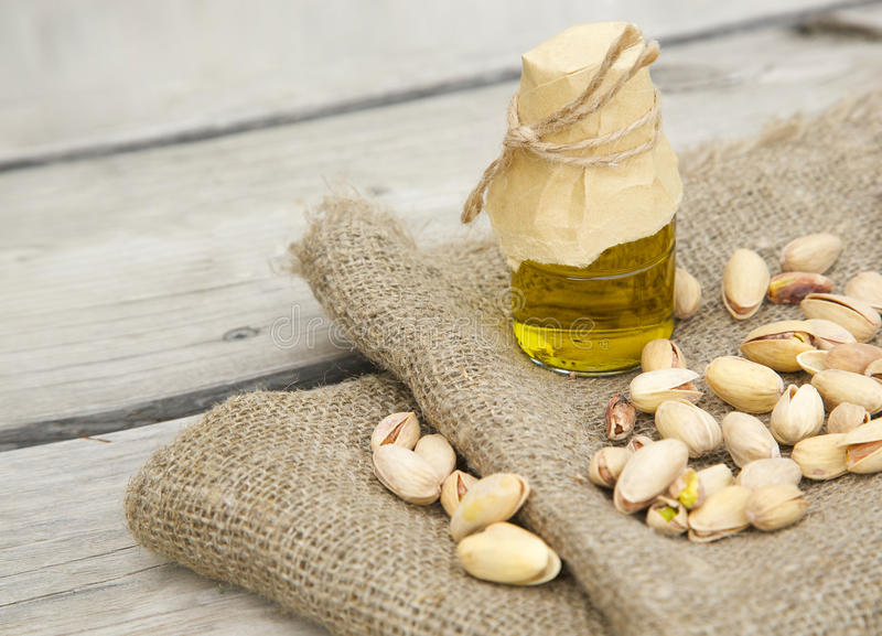 Pistachio nuts oil. Glass bottle of pistachio nuts oil on a grey sackcloth royalty free stock photography