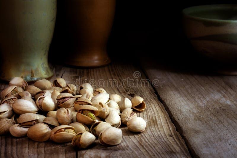 Pistachio nuts on old dark wood stock image