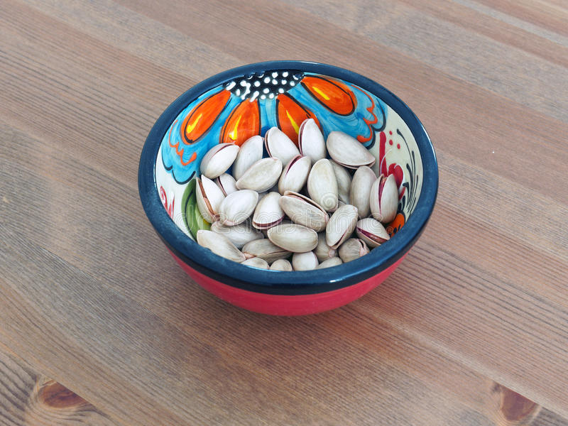 Pistachio Nuts in Red Spanish Bowl stock photography