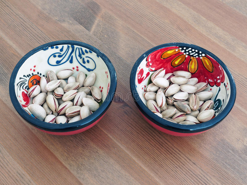 Pistachio Nuts in Red Spanish Bowls. Roasted pistachio nuts in shell in a small red Spanish snack bowls with flower designs, on a clear stained wood table. The stock photography