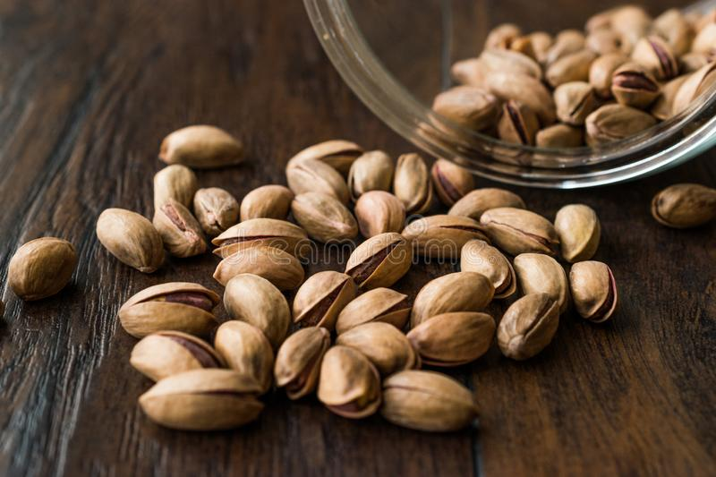 Pistachio Nuts with Shell on Dark Wooden Surface. Organic Snacks royalty free stock photo