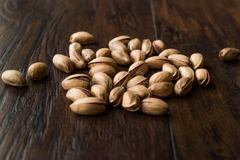 Pistachio Nuts with Shell on Dark Wooden Surface. Organic Snacks stock photo