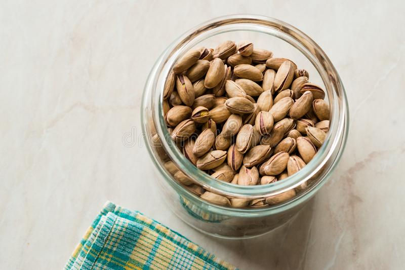 Pistachio Nuts with Shell in Jar / Glass Bowl. Organic Snacks royalty free stock images