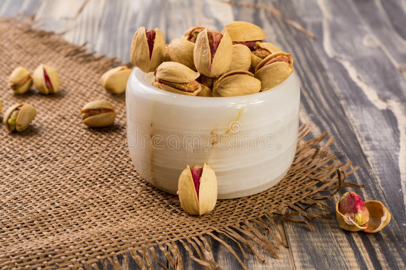 Pistachio Nuts. Spilling out of small stone bowl royalty free stock images