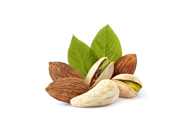Pistachio nuts wits cashew, almonds and leaves in closeup isolated. Mix of nuts royalty free stock image
