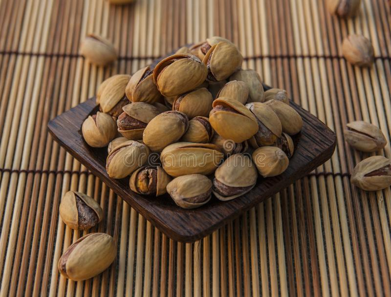 Pistachio nuts background. Pistachio nuts on wooden background royalty free stock image