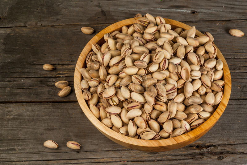 Pistachio nuts in a wooden bowl. On a rustic wooden table stock images