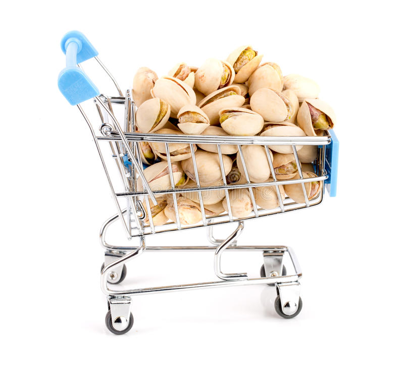 Pistachio in a shopping cart isolated on white background royalty free stock photos