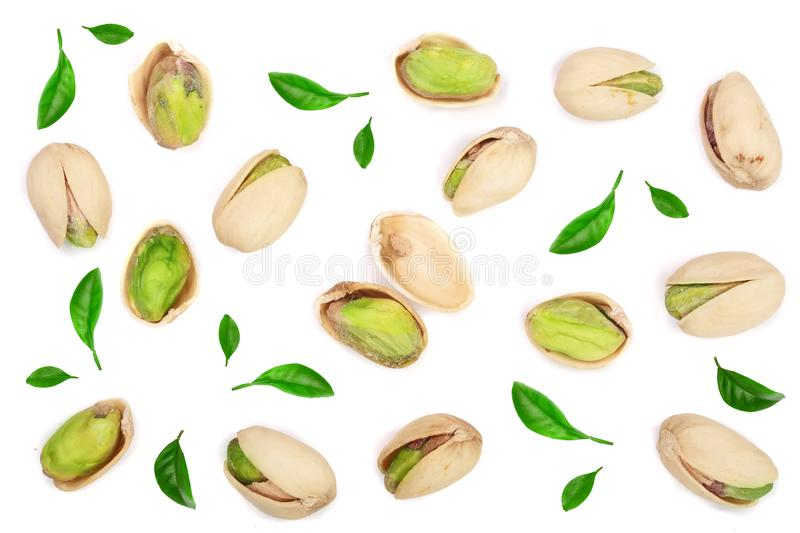Pistachios decorated with green leaves isolated on white background, top view. Flat lay pattern stock images