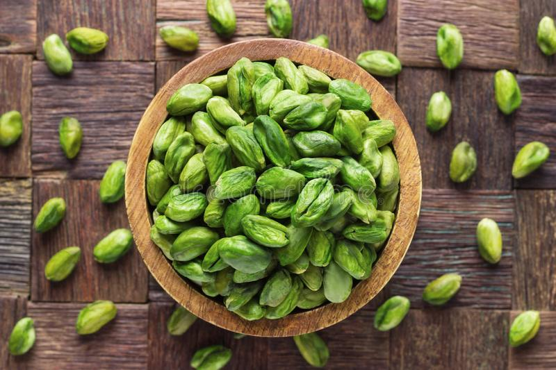 Pistachios nuts peeled green in wooden bowl, top view royalty free stock photos