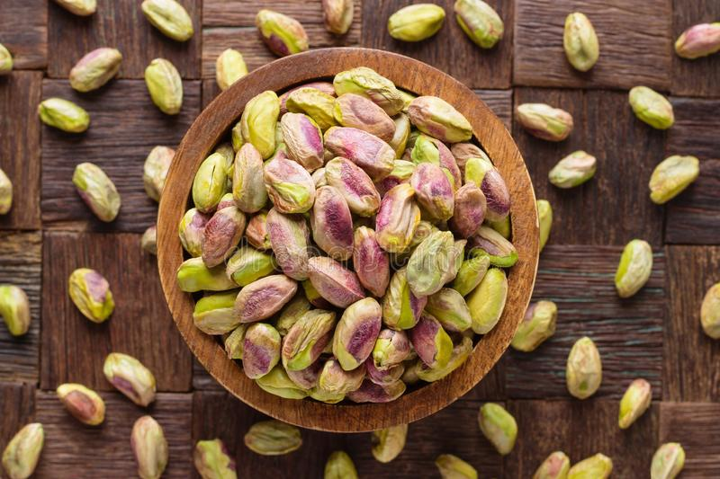 Pistachios nuts peeled in wooden bowl, top view royalty free stock photos