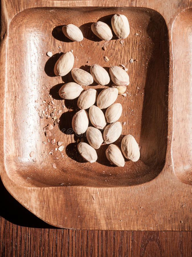 Pistachios nuts in wooden bowl. Unhealthy food. stock images