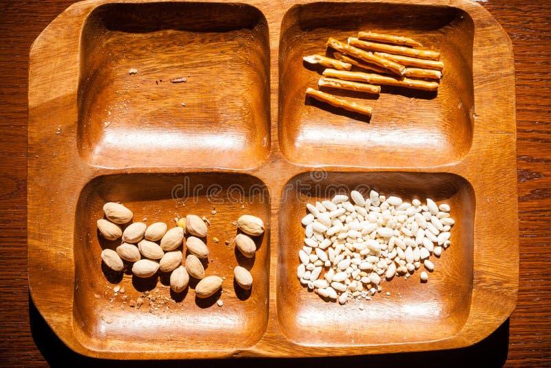 Pistachos, arroz asado y palillos salados en cuenco fotografía de archivo