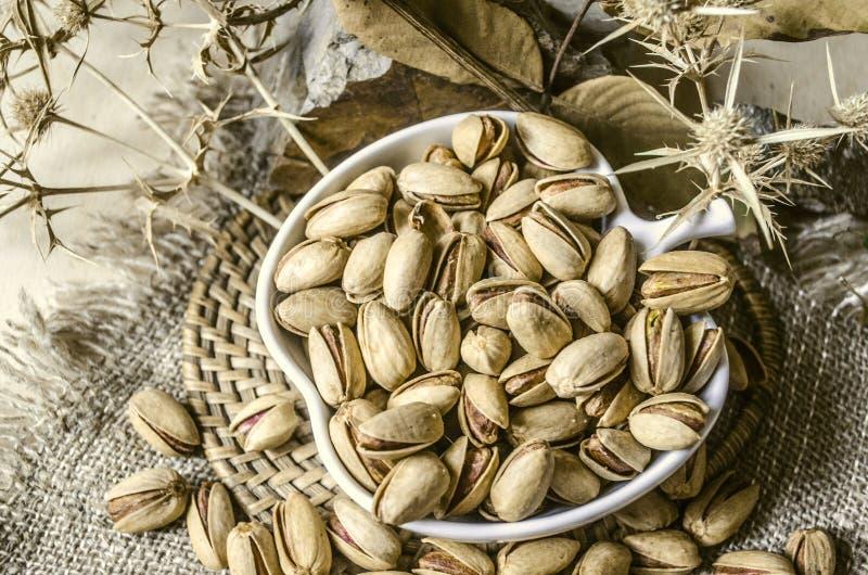 Pistacje smażyli z solą w białej filiżance na słomianym round półmisku zdjęcie stock
