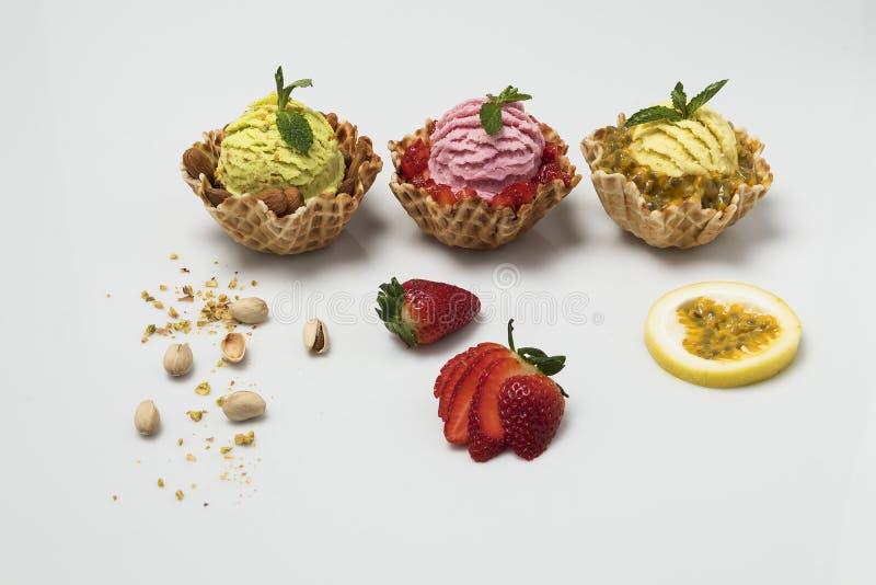 Pistacjowego pation owocowi i truskawkowi lody na białym tle z towarzyszyć owoc zdjęcia royalty free