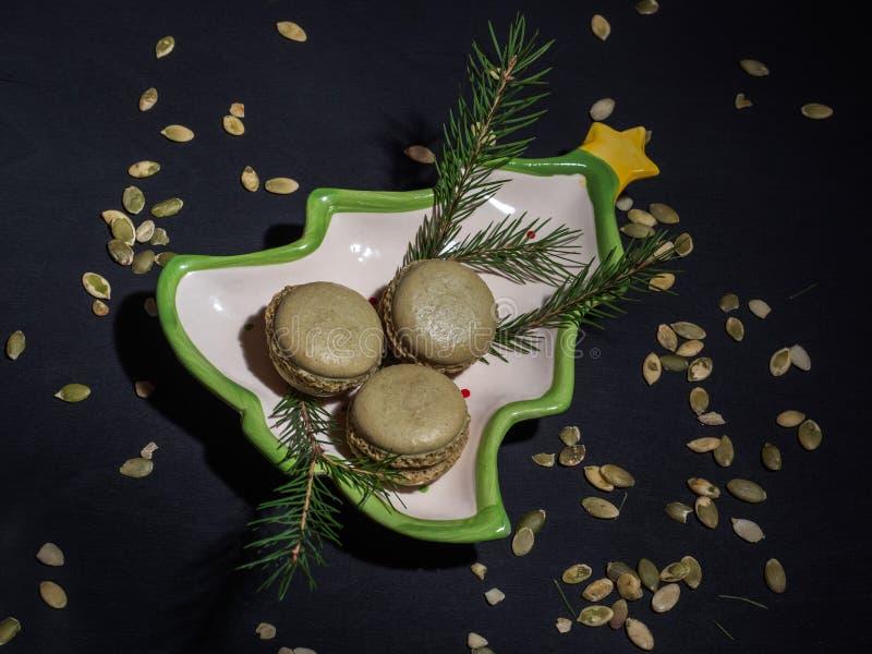 Pistacjowi macarons na nowego roku talerzu na ciemnym tle, rozrzucanie dyniowi ziarna tła błękit gałąź sezonu nieba świerczyny zi fotografia stock