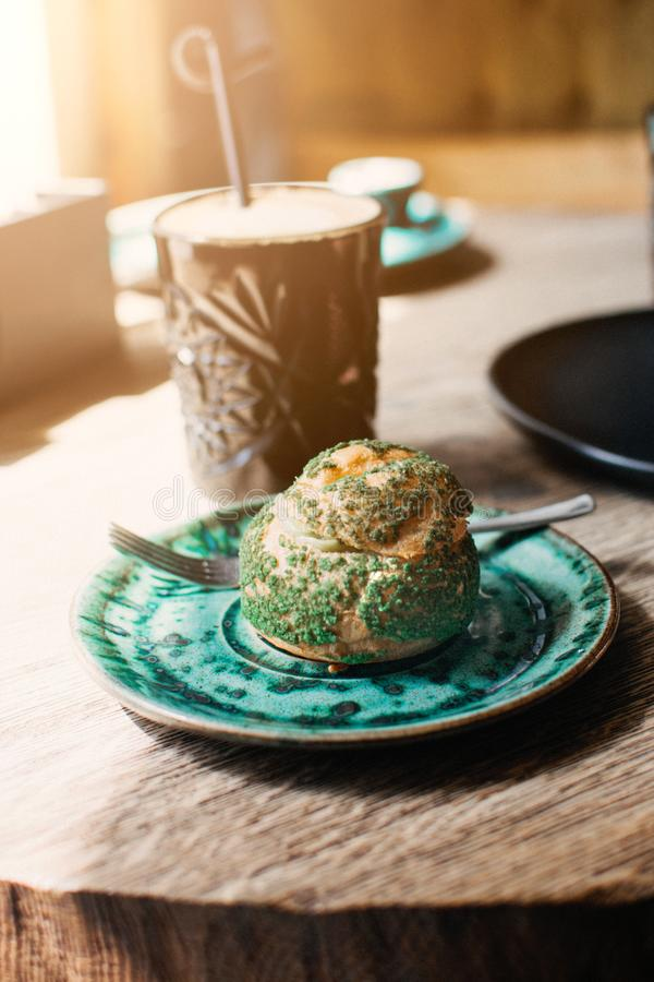 Pistacjowy eclair, profiterole w glazerunku na zieleń talerzu na stole, zakończenie w górę Eclair, custard tarta z pistacjową śmi zdjęcie royalty free