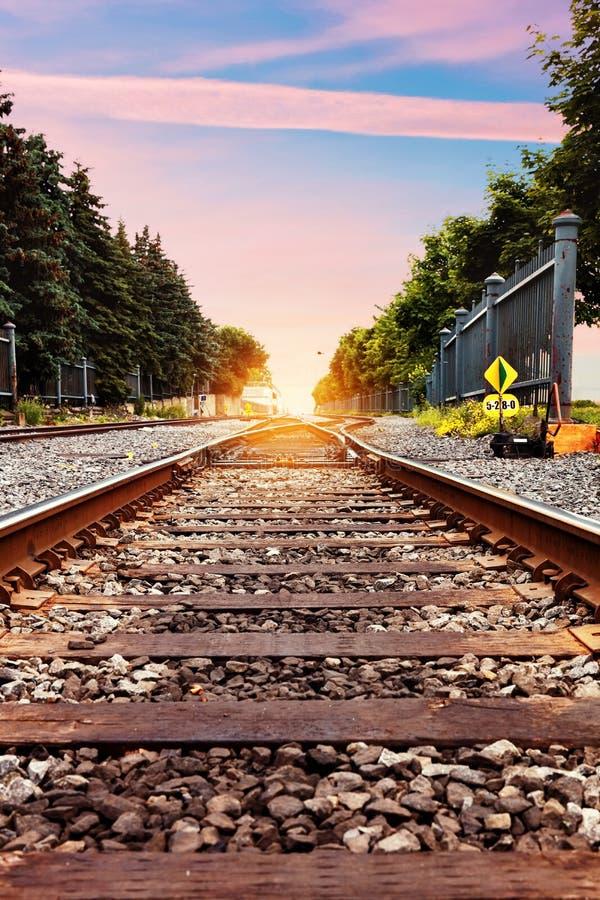 Pistas de ferrocarril contra el cielo hermoso en la puesta del sol imagen de archivo