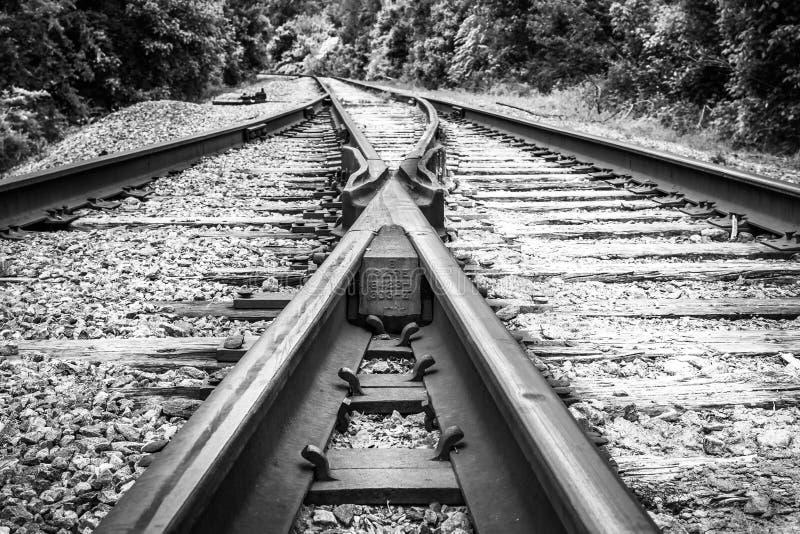 Pistas de ferrocarril de divergencia marrones negras y blancas imagen de archivo