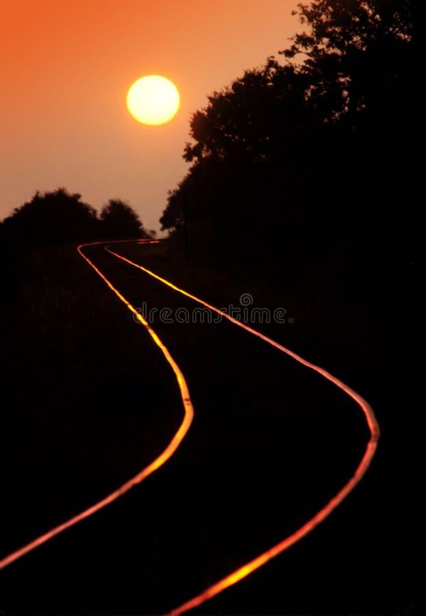 Pistas de ferrocarril en puesta del sol fotos de archivo
