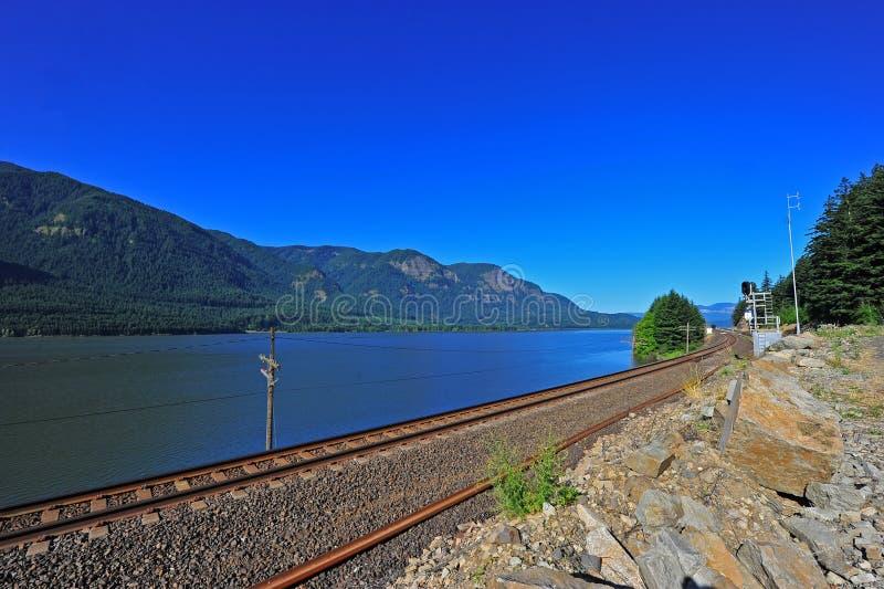 Pistas de ferrocarril a lo largo de un río fotografía de archivo libre de regalías