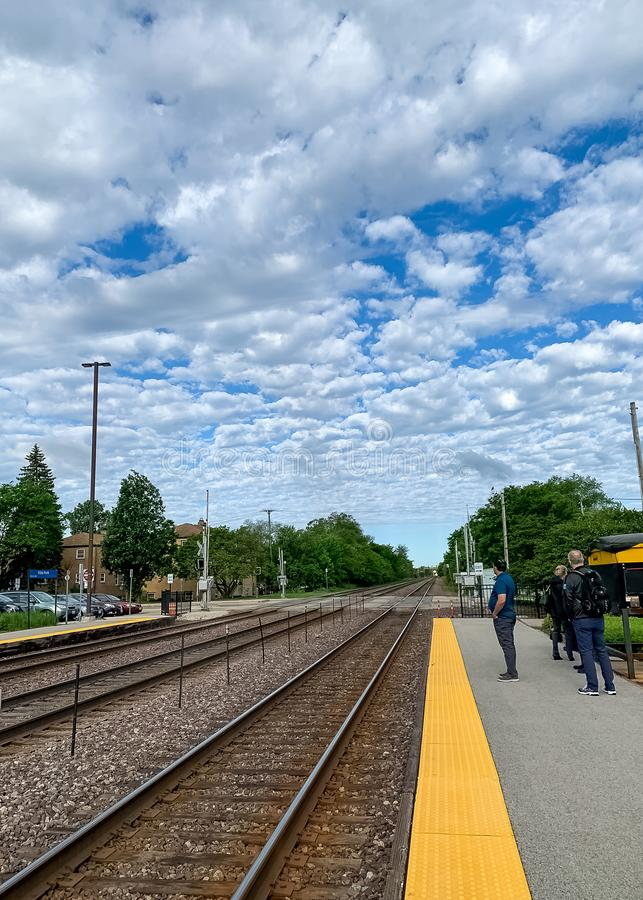 Pistas de ferrocarril que desaparecen el punto en un cielo nube-llenado estrato imagen de archivo