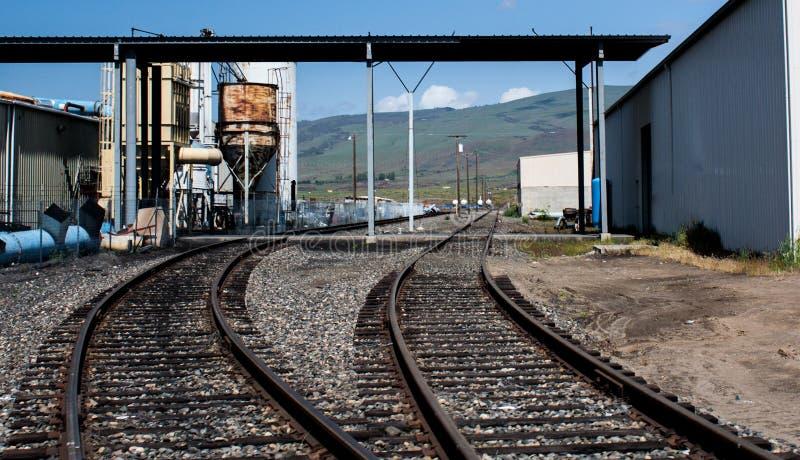2 pistas de ferrocarril que llevan adentro a un cargamento que descarga la instalación imagen de archivo libre de regalías