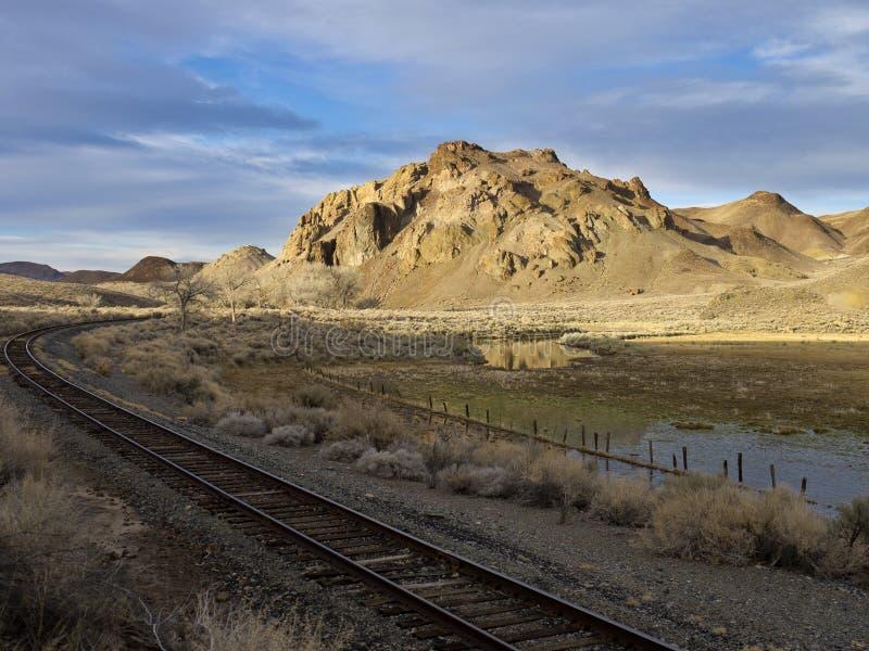 Pistas de ferrocarril que se ejecutan más allá de un rancho del desierto fotografía de archivo libre de regalías