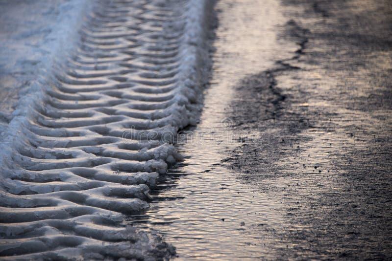 Pistas de los neumáticos en nieve de fusión imagen de archivo