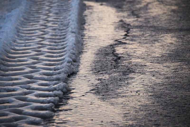 Pistas de los neumáticos en nieve de fusión imágenes de archivo libres de regalías